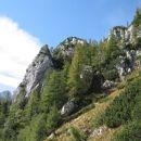 v smeri dveh izrazitih vrhov, pred poraščenim skalnim grebenčkom desno navzgor