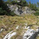 po strmih travah do skal in tik pod njimi levo