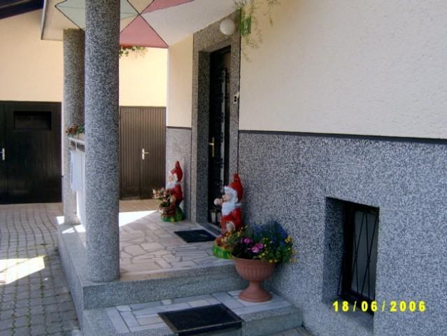 Palčki pred vhodom , v ozadju garaza in dervarnica