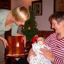 Filip odpira darila, ki mu jih je pod smrekico pustil Božiček.