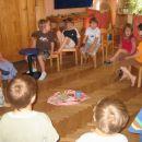 Vzgojiteljica vse otroke zbere v krog. S tihim glasom prepeva in otroci se sami posedejo.